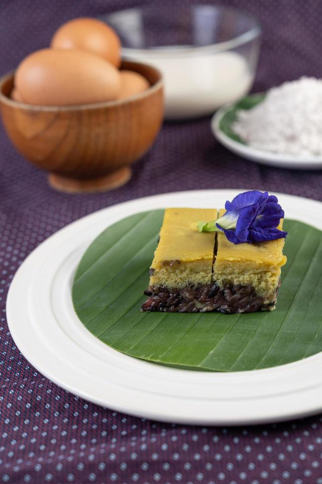 Black sticky rice on a banana leaf in a white plate with butterfly pea flowers photo