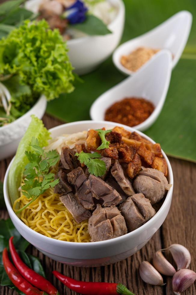 Yellow noodles with crispy pork and meatballs photo