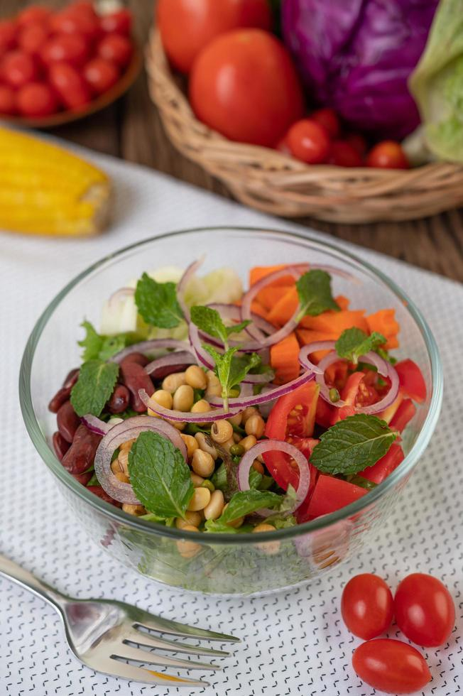 Fresh vegetable and fruit salad in a glass bowl photo