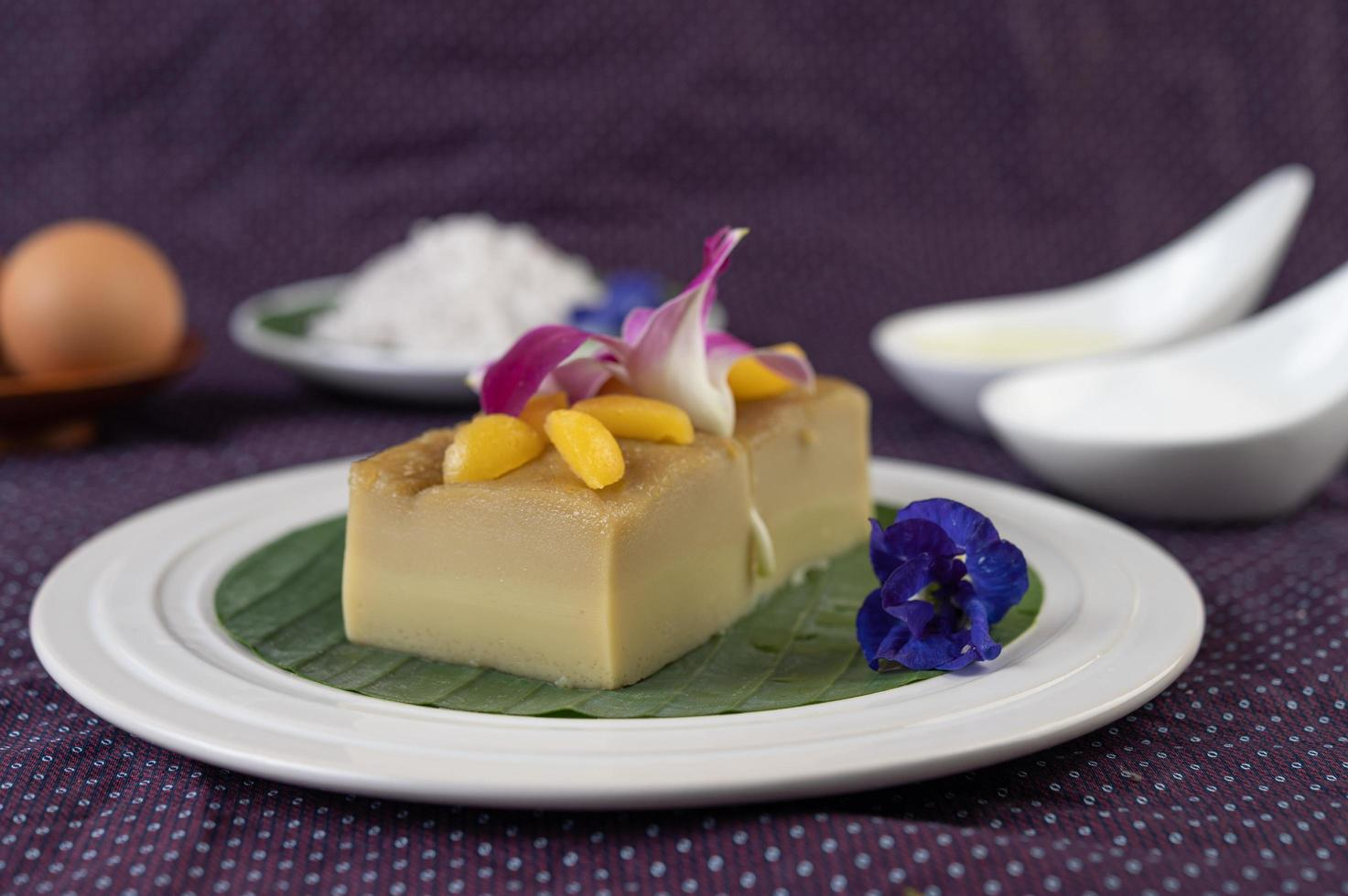 Custard on a banana leaf with pea flowers and orchids photo