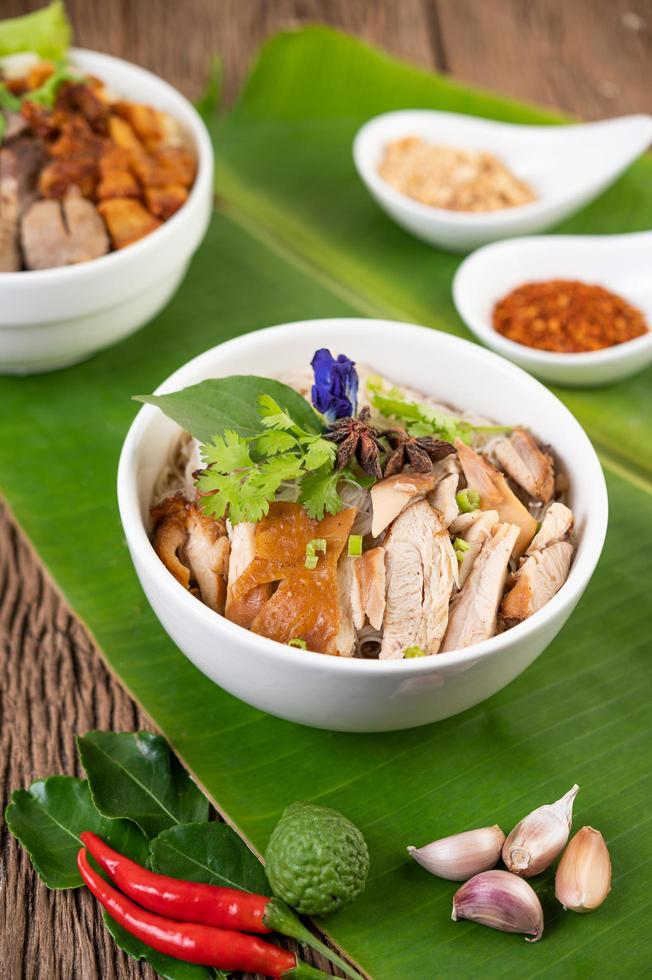 Chicken and noodles in a bowl with side dishes photo