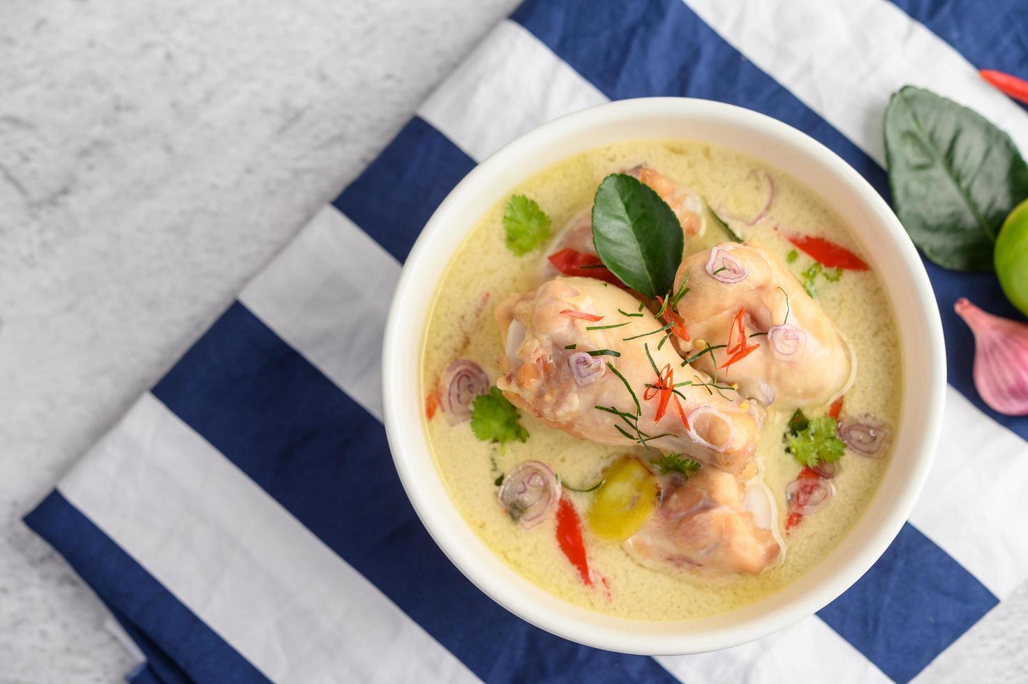tom kha kai, sopa de coco tailandesa sobre un paño azul foto