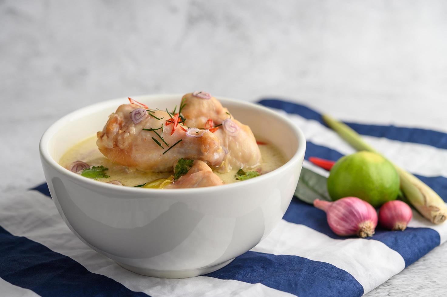 tom kha kai, sopa de coco tailandesa sobre un paño de rayas azules foto