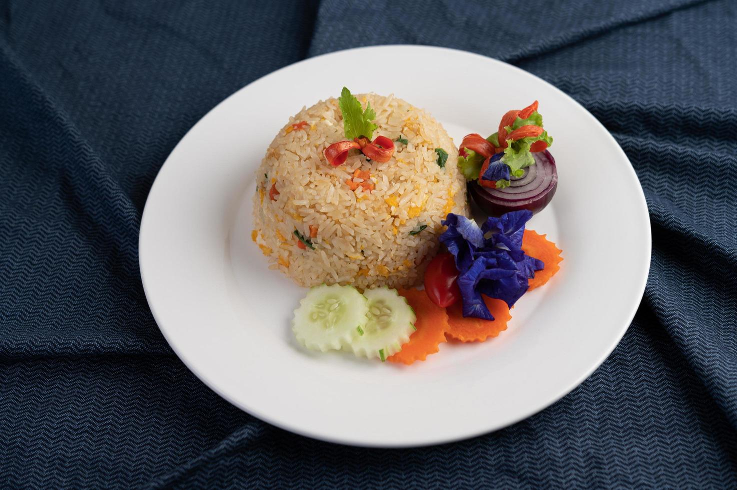 Egg fried rice on a white plate with wrinkled fabric photo