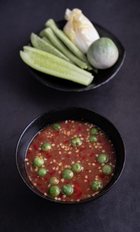 Shrimp-paste sauce in a black bowl with cucumber, beans and Thai eggplant photo
