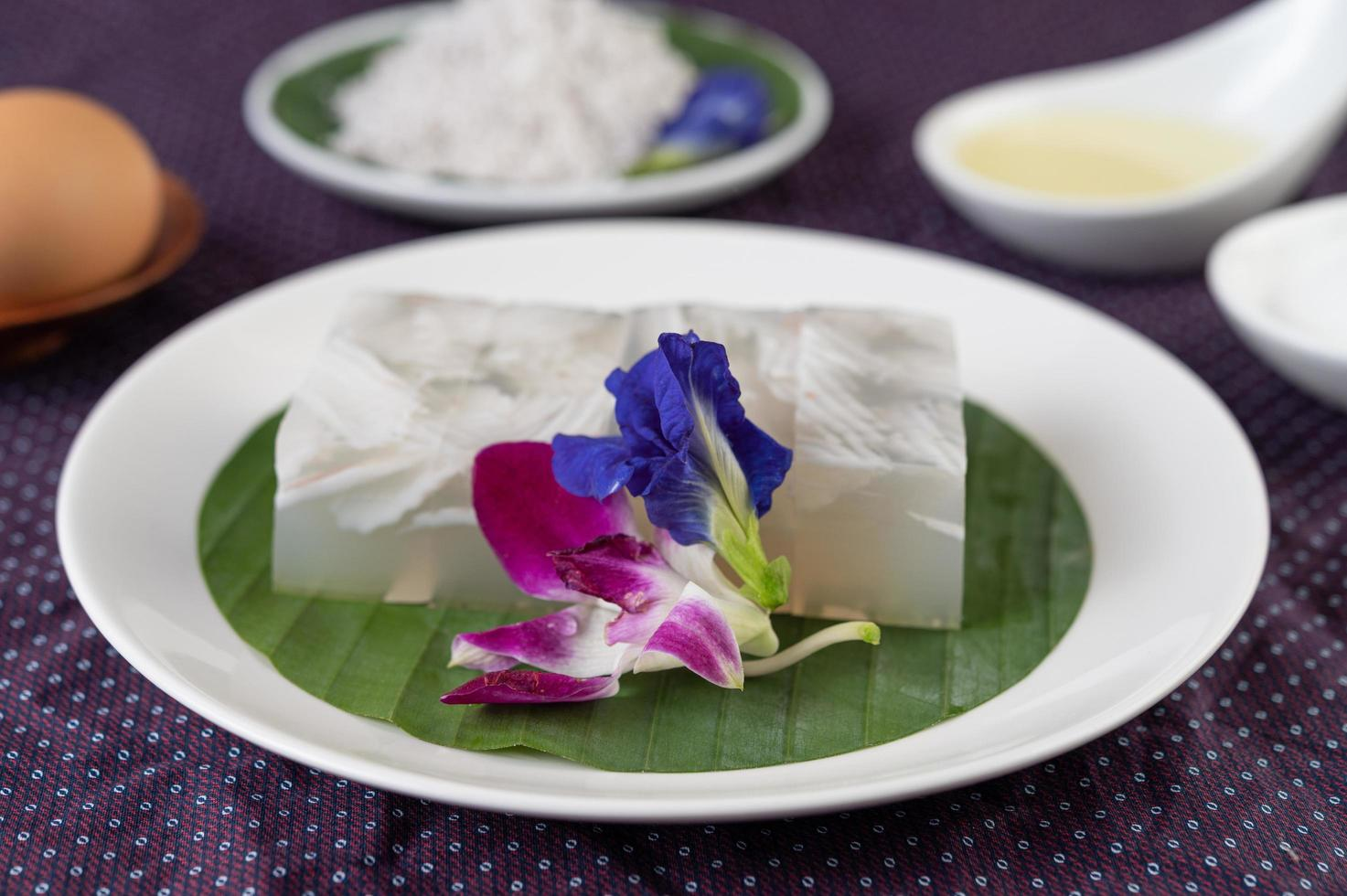 Coconut jelly on a banana leaf with butterfly pea flowers and orchids photo