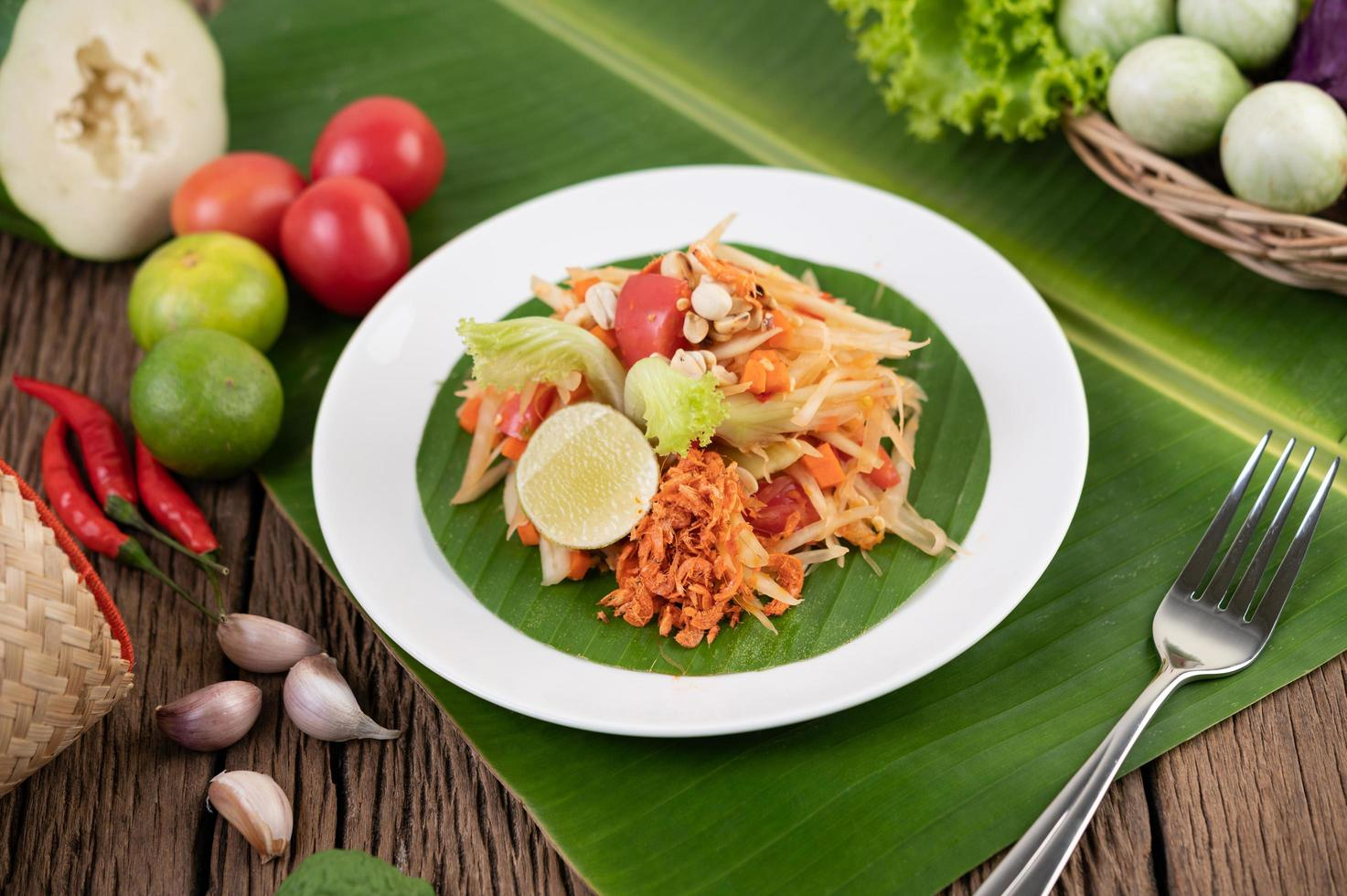Thai papaya salad with banana leaves and fresh ingredients photo