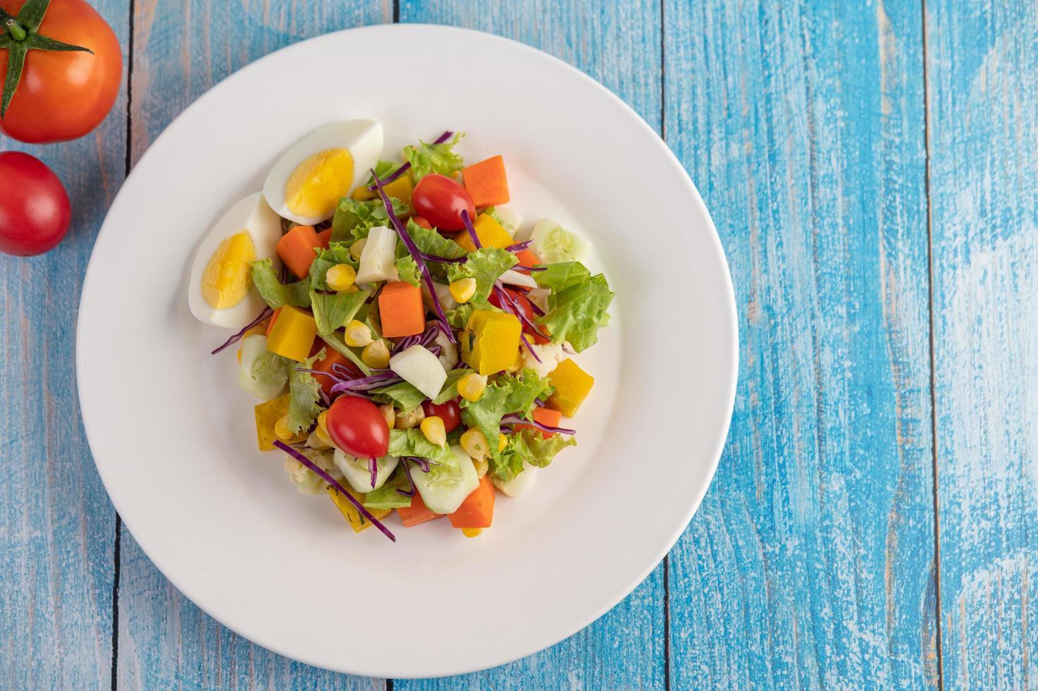Ensalada fresca en un plato blanco con un sándwich y tomates foto