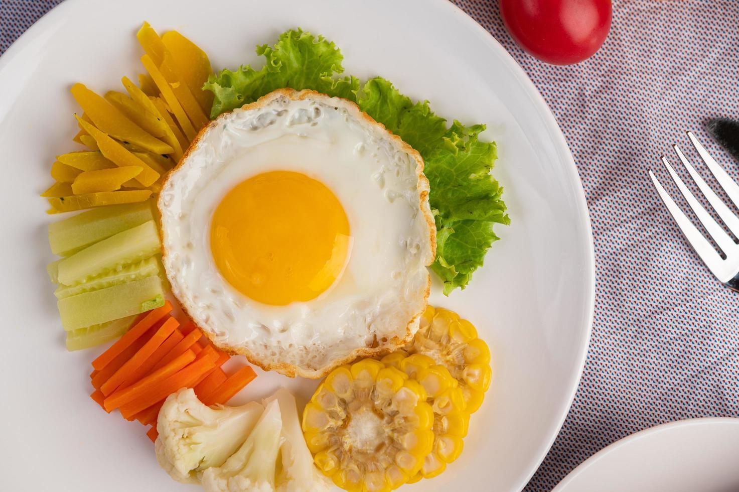 Fried egg, salad, pumpkin, cucumber, carrot, corn, cauliflower, tomato and toast photo