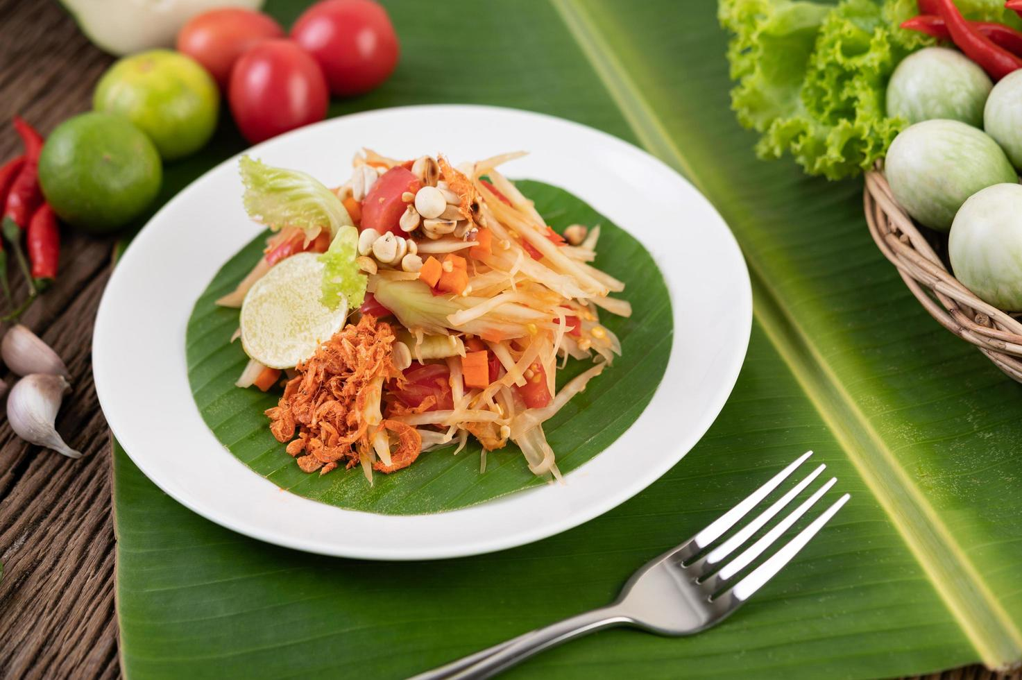 Ensalada tailandesa de papaya con hojas de plátano e ingredientes frescos foto