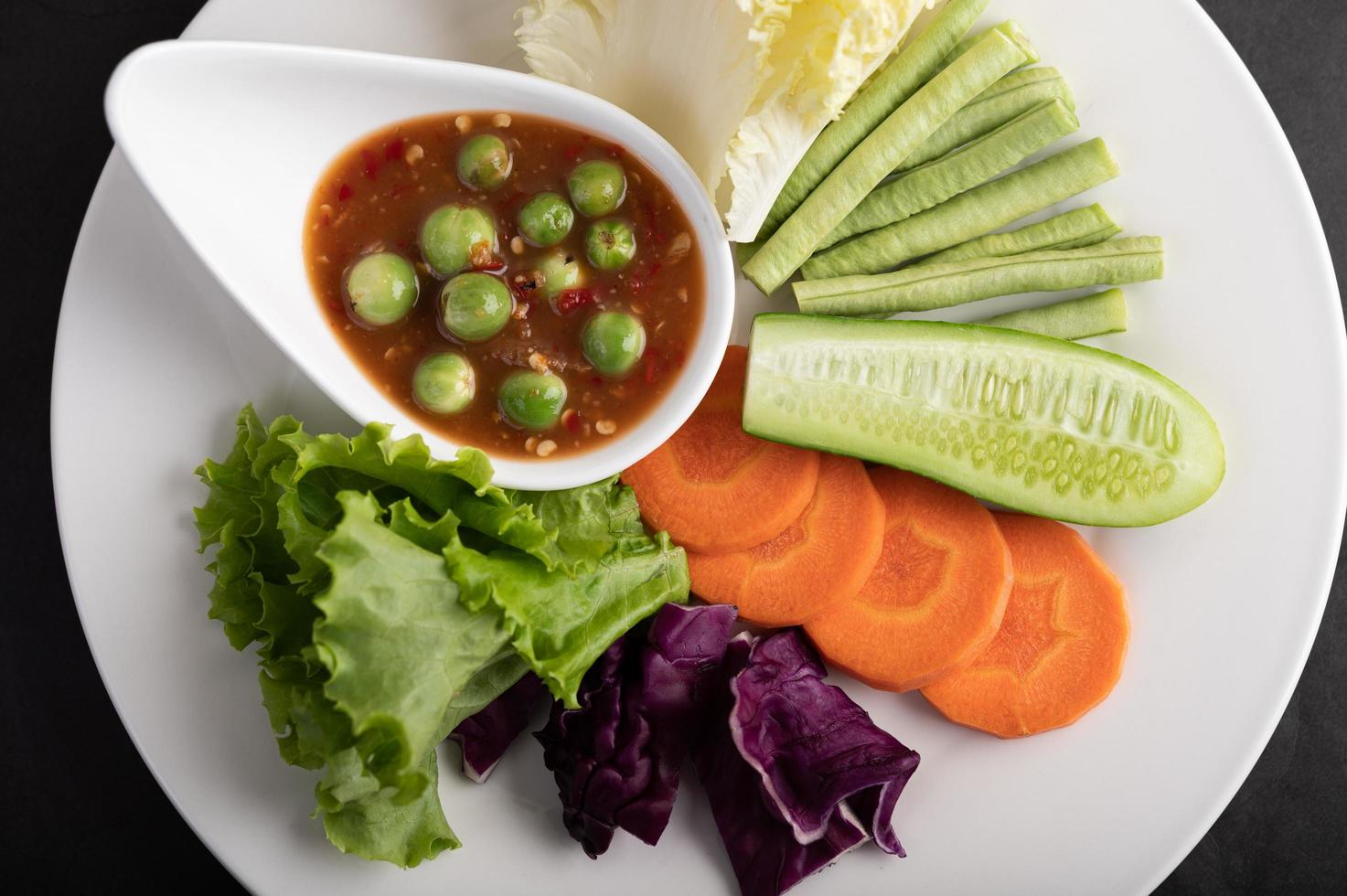 Sauce in a bowl with vegetables photo