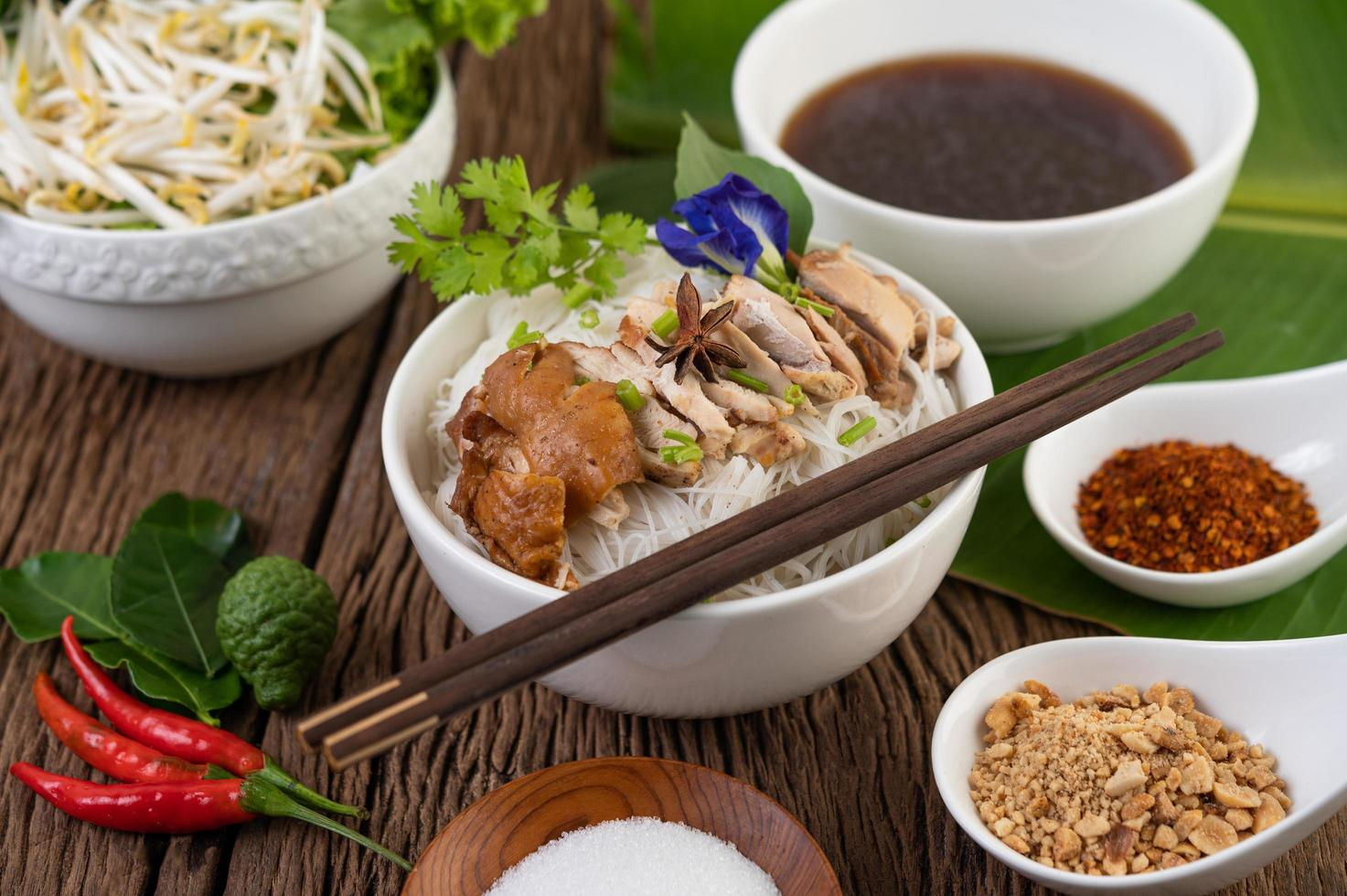 Chicken noodles in a bowl with Thai side dishes photo