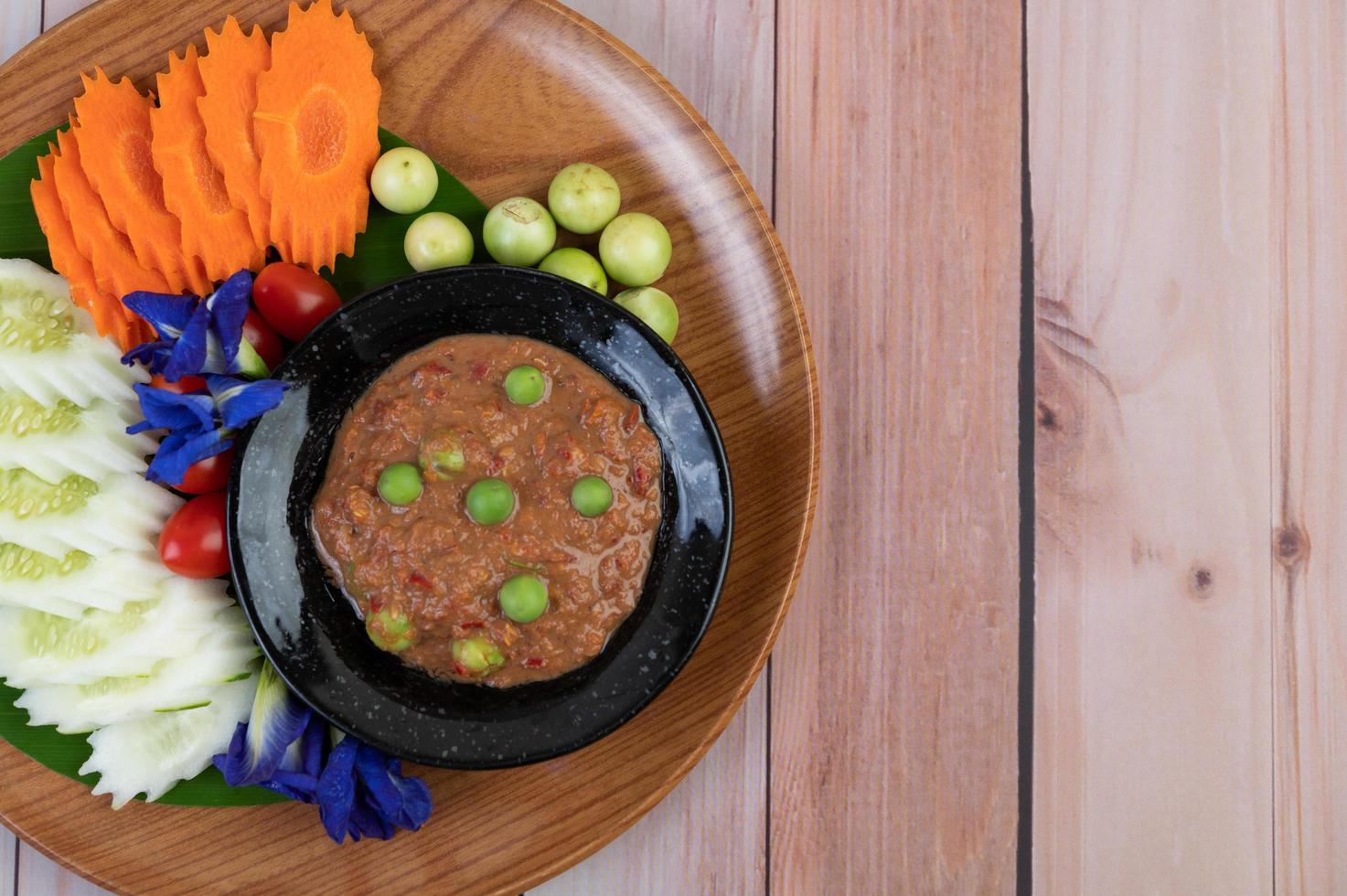 Pasta de chile en un bol con berenjenas, zanahorias, chile y pepinos en una canasta foto