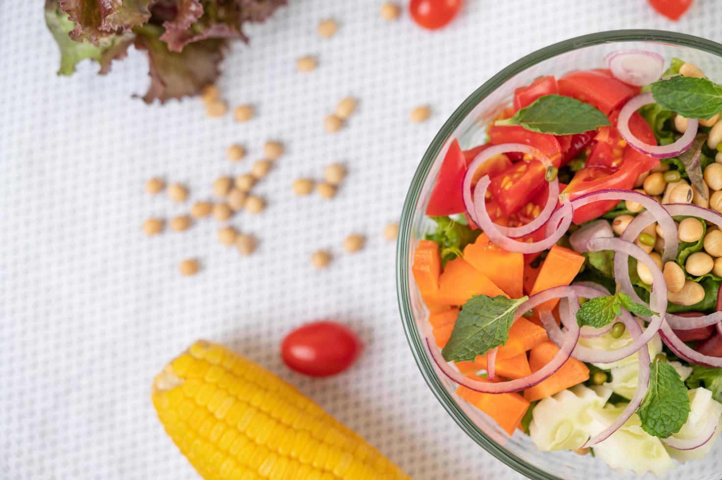 Ensalada de frutas y verduras frescas en un recipiente de vidrio foto
