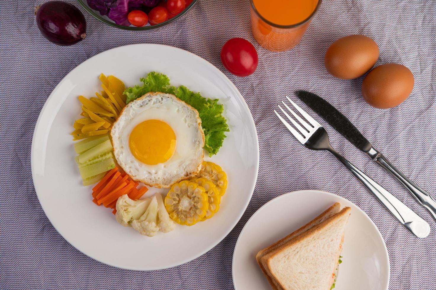 Desayuno de huevo frito con verduras y jugo. foto