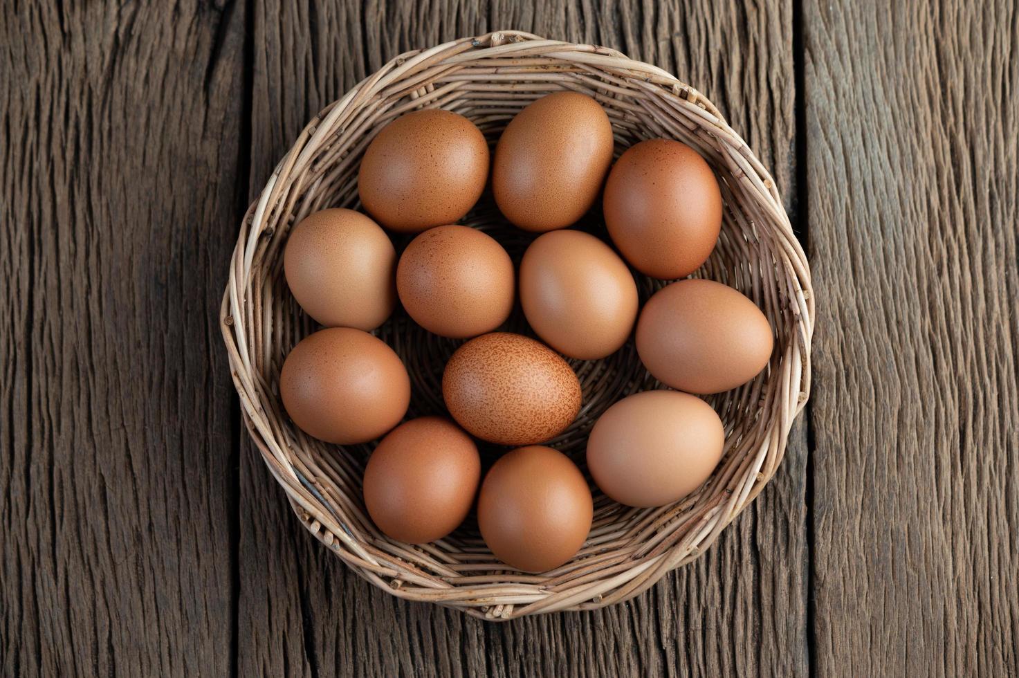 puso huevos en una canasta de madera foto