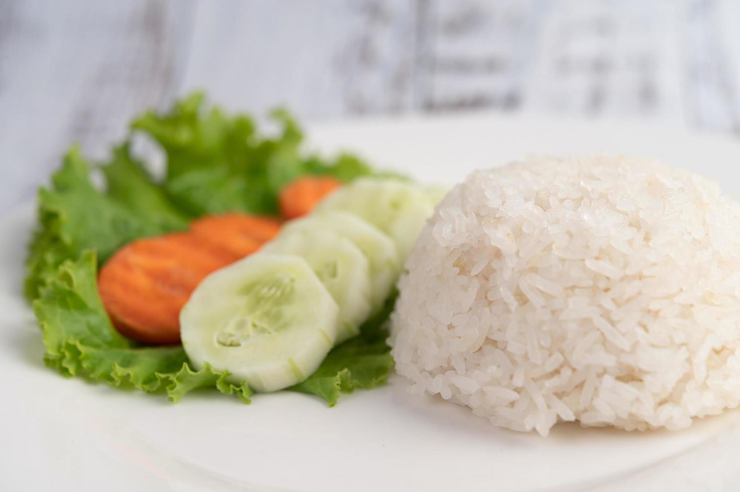 Steamed rice with cucumber, salad and carrots photo