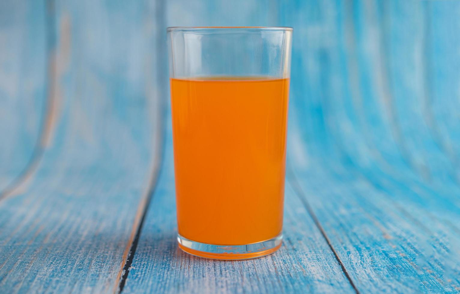 jugo de naranja en el piso de madera azul foto