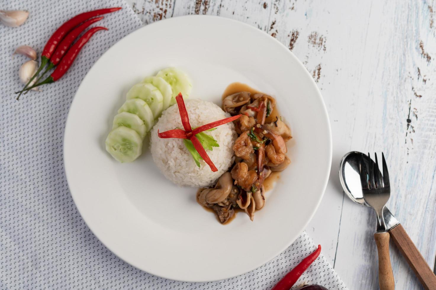 arroz cubierto con albahaca salteada con calamares y camarones foto