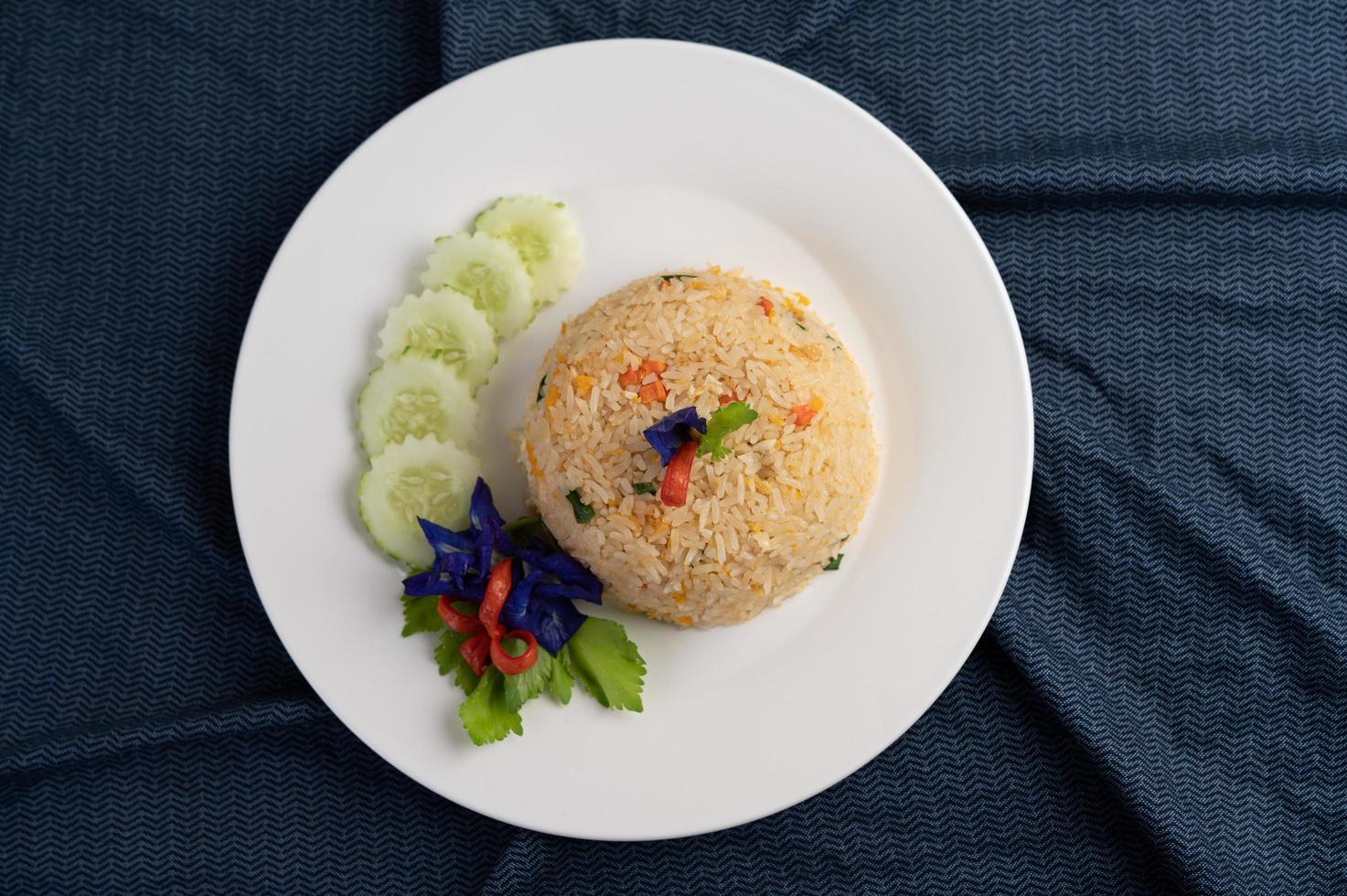 Arroz frito con huevo en un plato blanco con tela arrugada foto