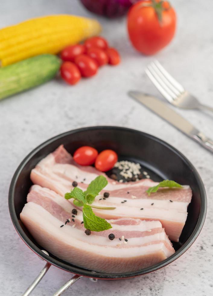 panceta de cerdo en una sartén con semillas de pimiento, tomates y especias foto