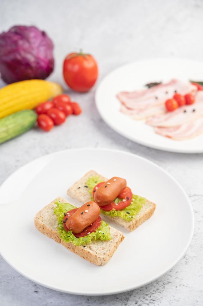 salchicha con tomate y ensalada en pan foto