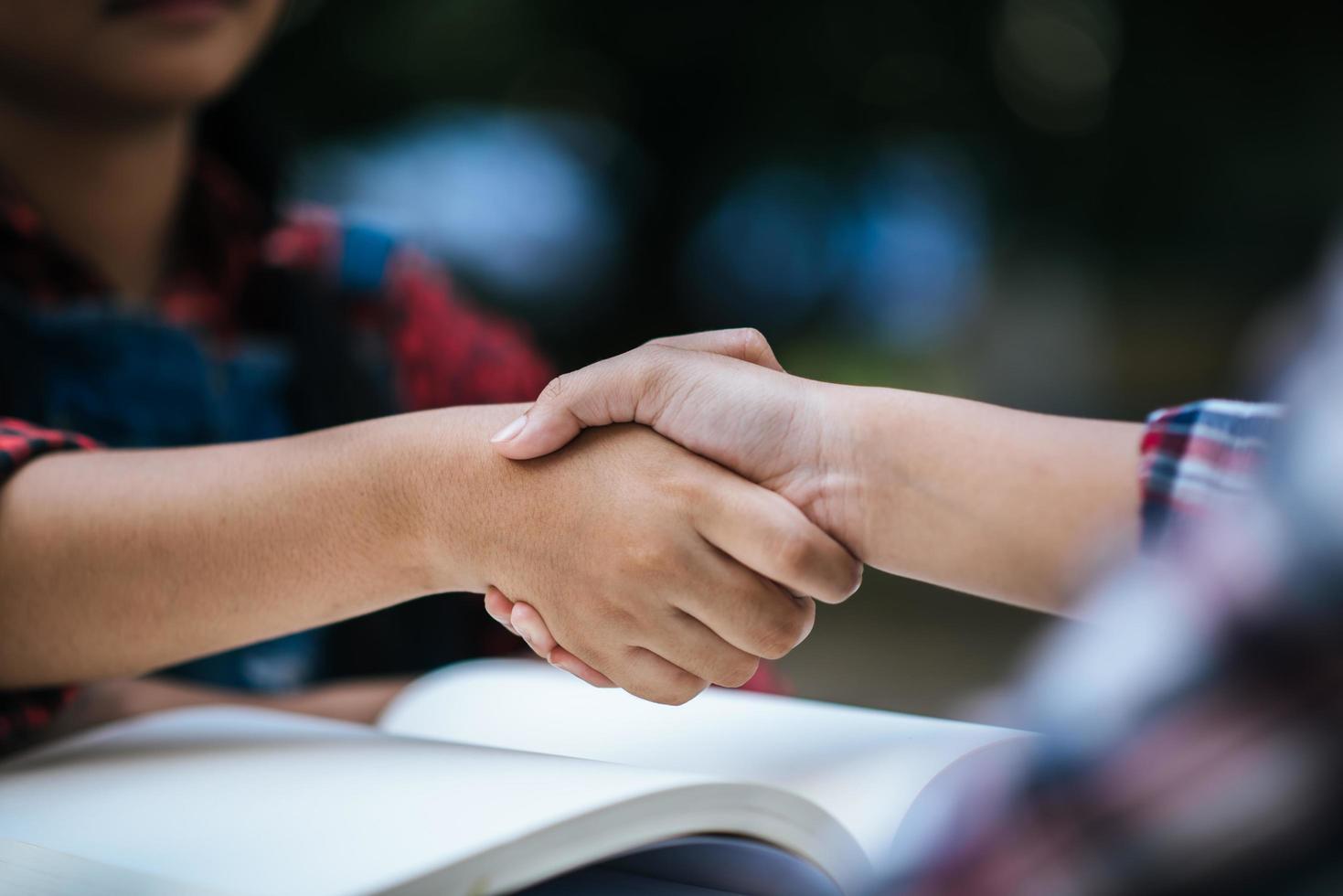 jóvenes estudiantes universitarios se dan la mano en el parque escolar foto