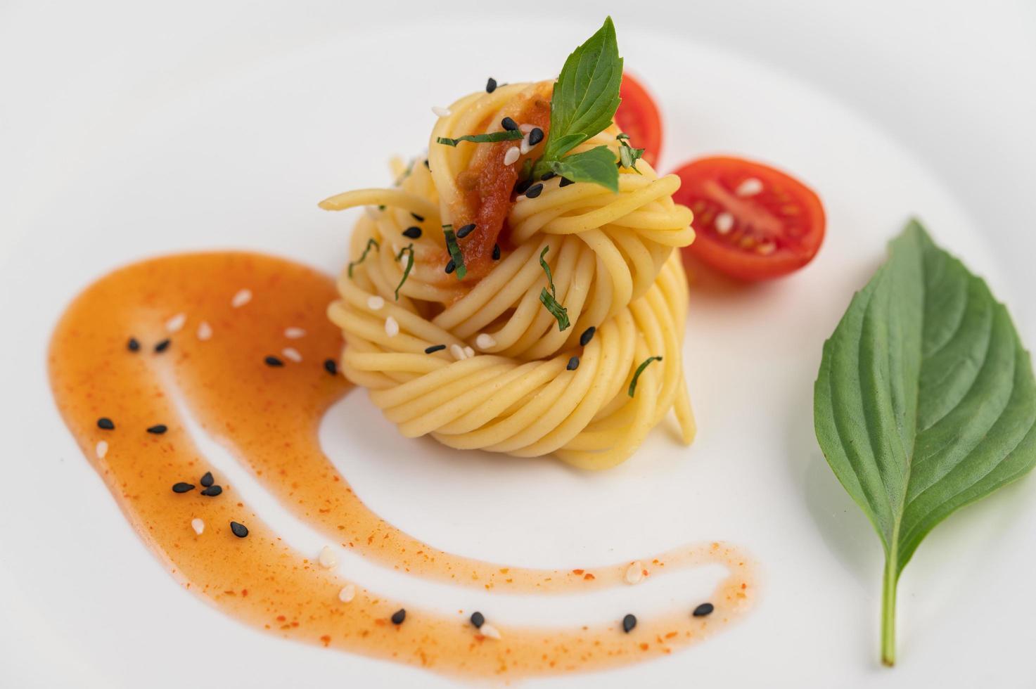 espaguetis gourmet bellamente dispuestos en un plato blanco foto