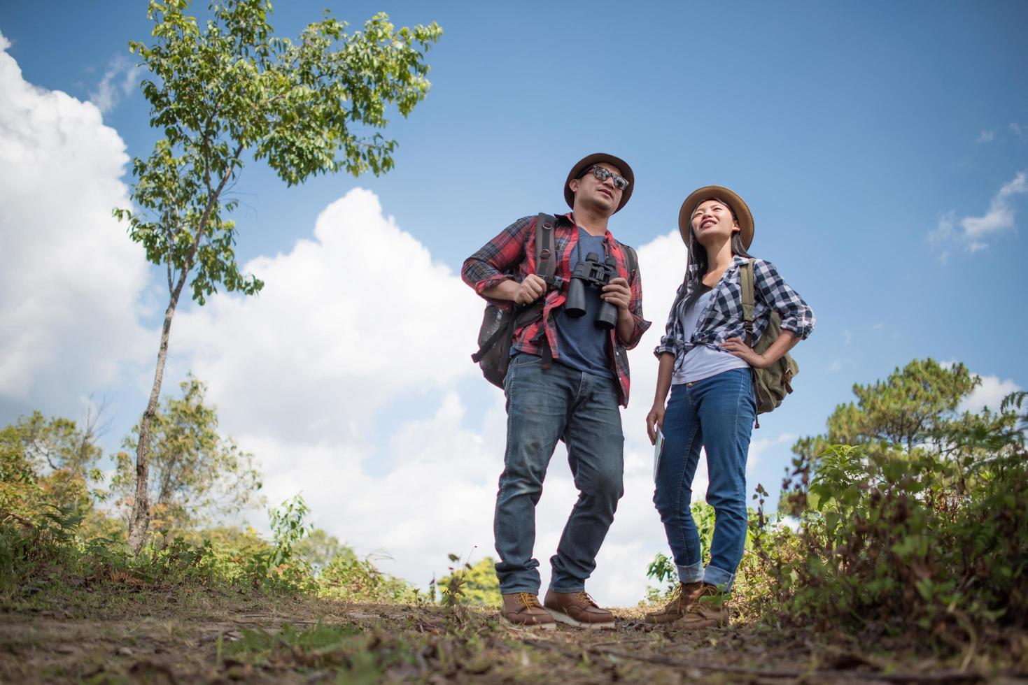 Two young travelers with backpacks in green jungle photo