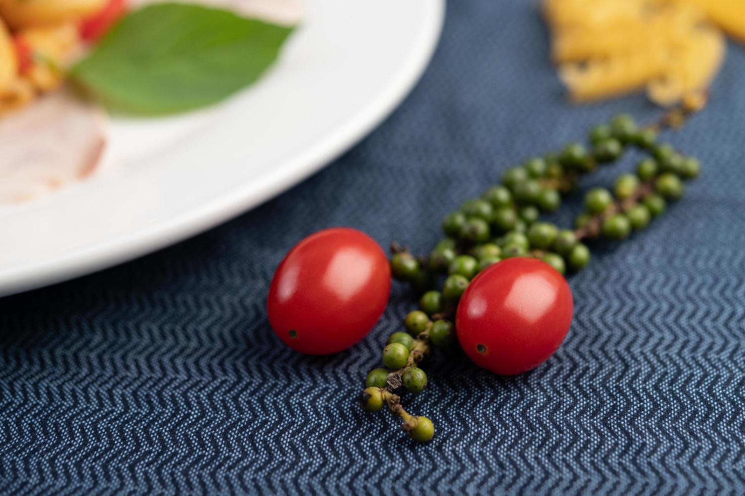 tomates y semillas de pimiento fresco sobre una tela estampada foto
