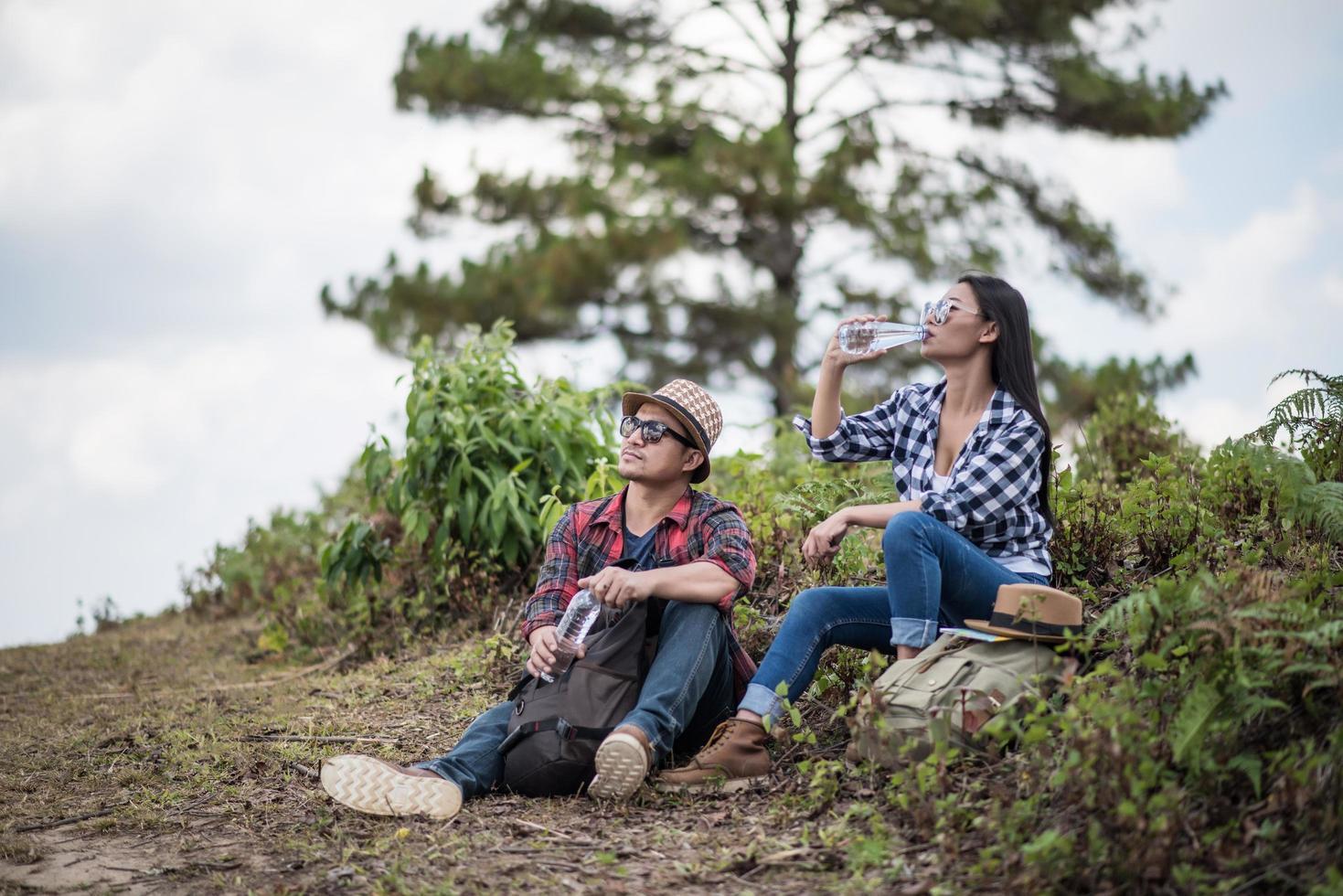 jóvenes excursionistas bebiendo agua en el bosque foto