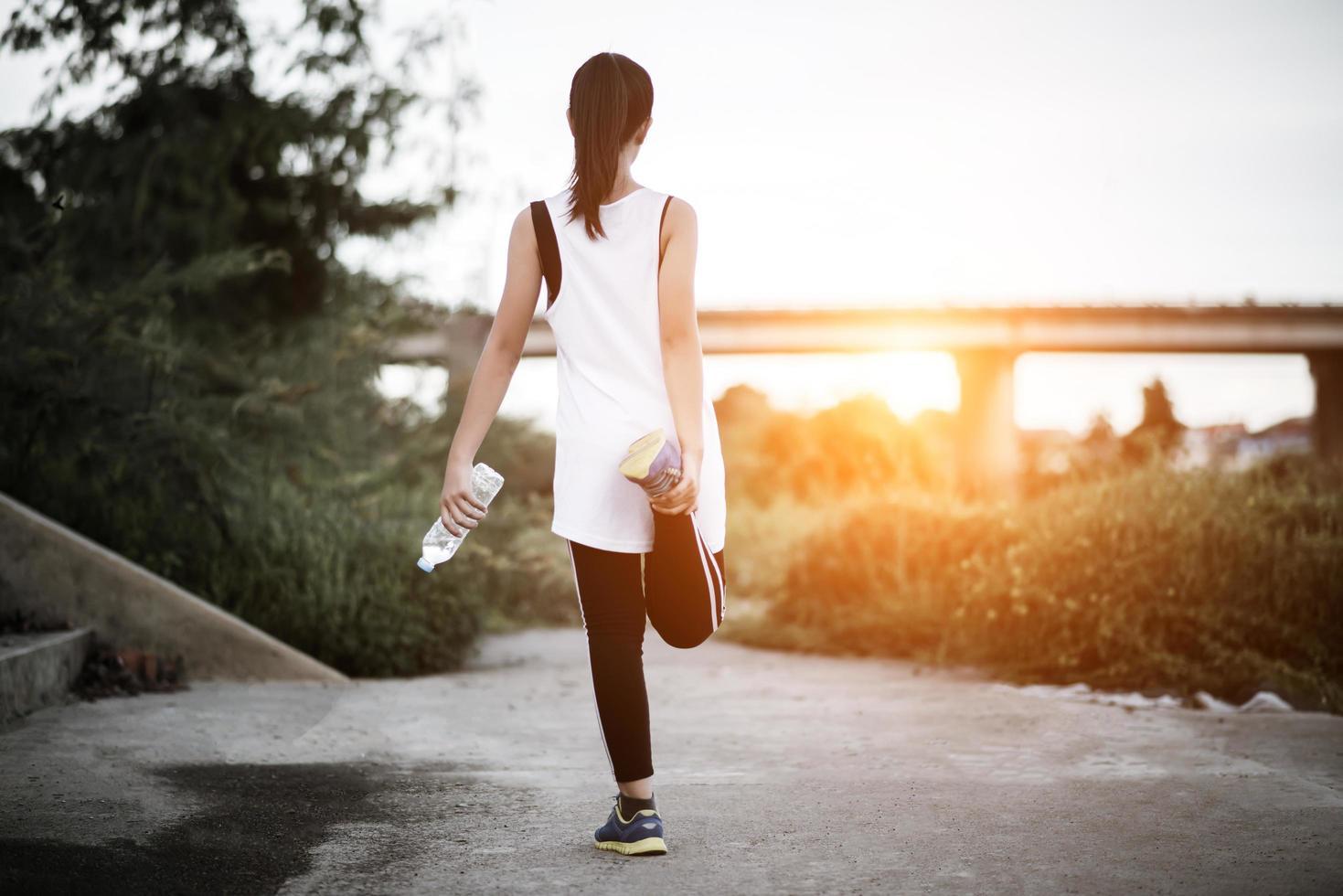 Joven adolescente fitness sosteniendo una botella de agua después de ejecutar el ejercicio foto