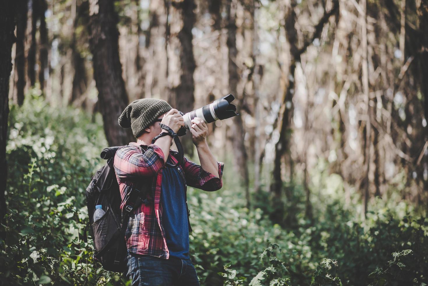 joven fotógrafo tomando fotos en el bosque