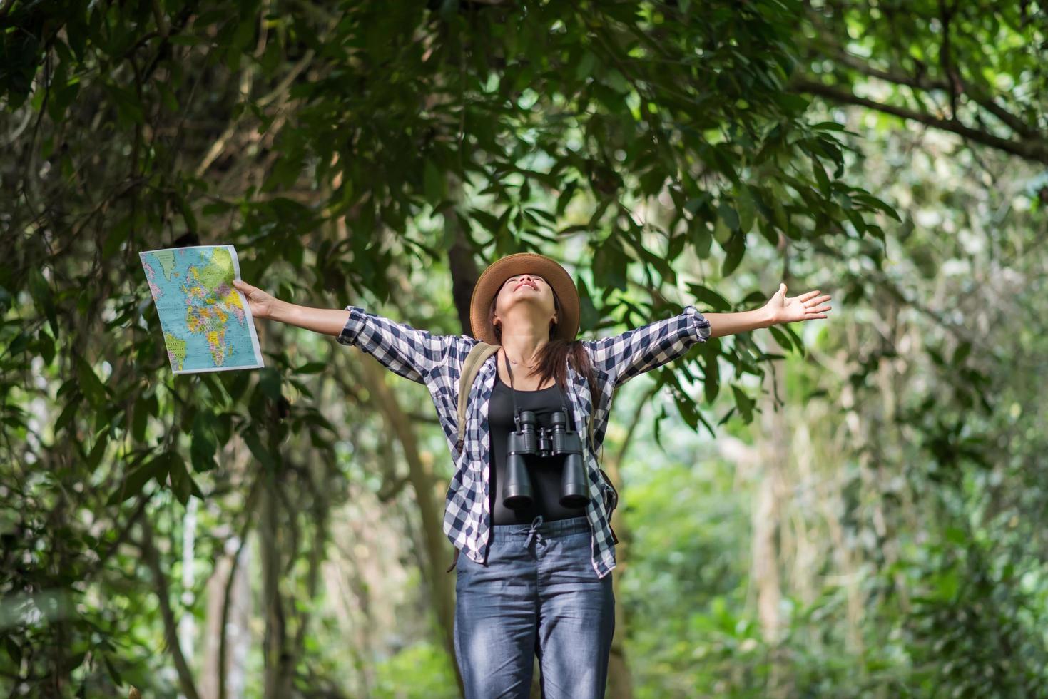 Happy adventurous young woman watching wildlife with binoculars in nature photo