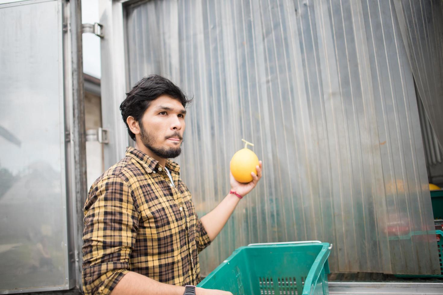Retrato de un agricultor hipster sosteniendo una caja de frutas para la venta en el mercado foto