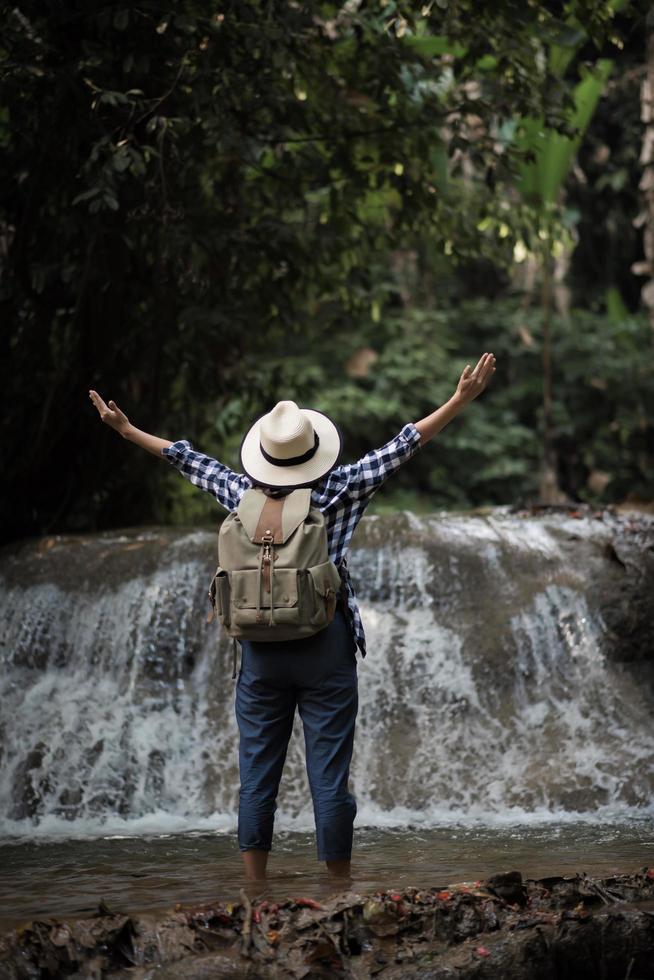 Mujer joven divirtiéndose bajo una cascada en el bosque foto