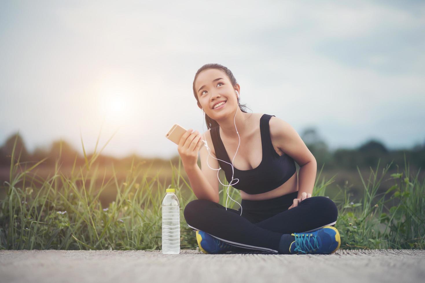 Adolescente fitness con auriculares escuchando música durante su entrenamiento foto