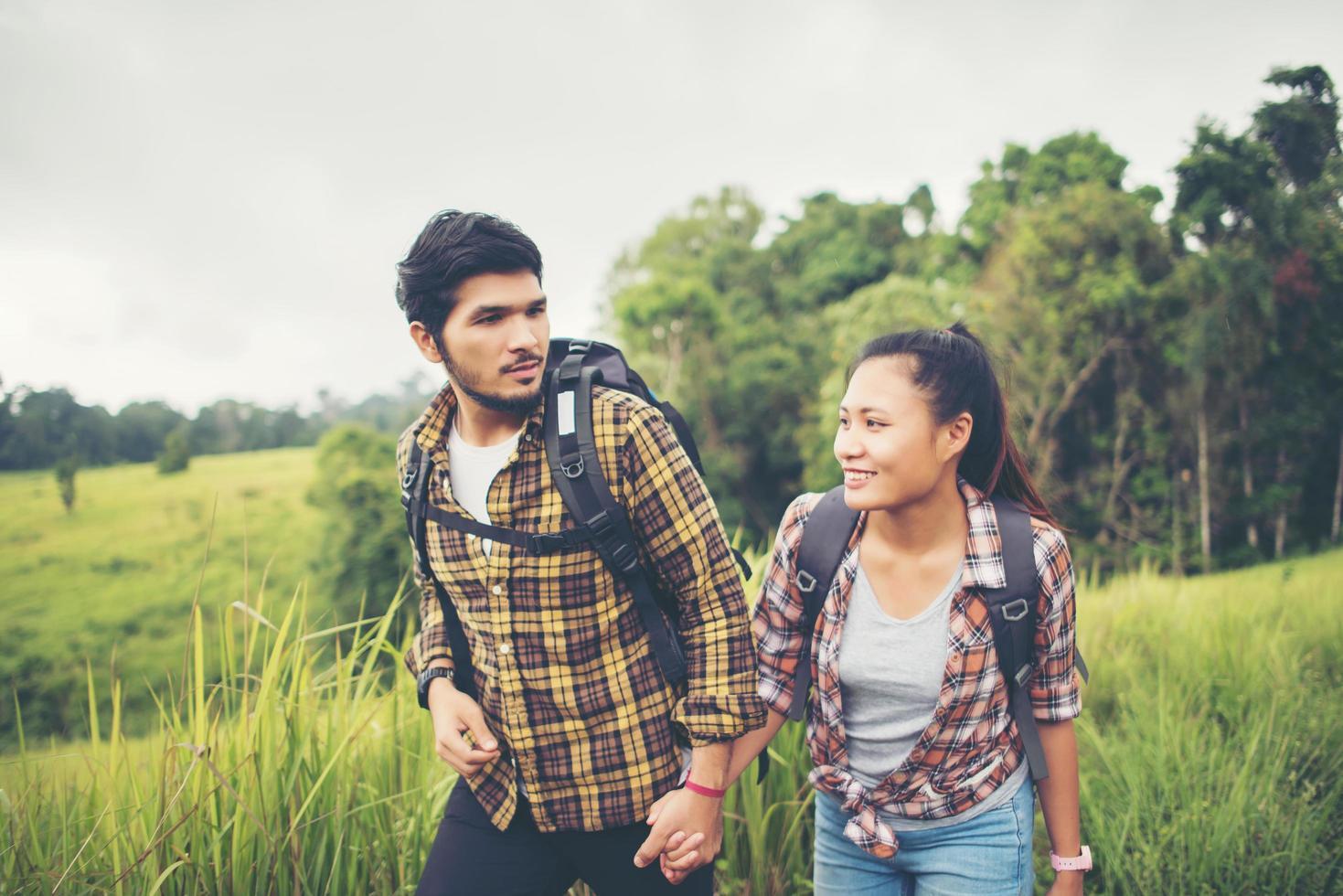 Retrato de una joven pareja feliz caminando en un viaje de senderismo foto