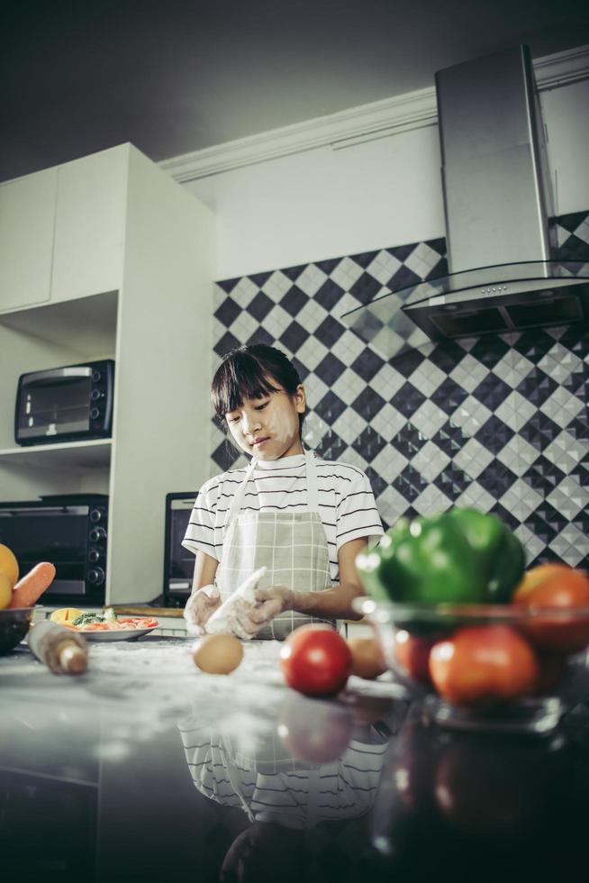 linda niña amasa masa de harina en la cocina foto