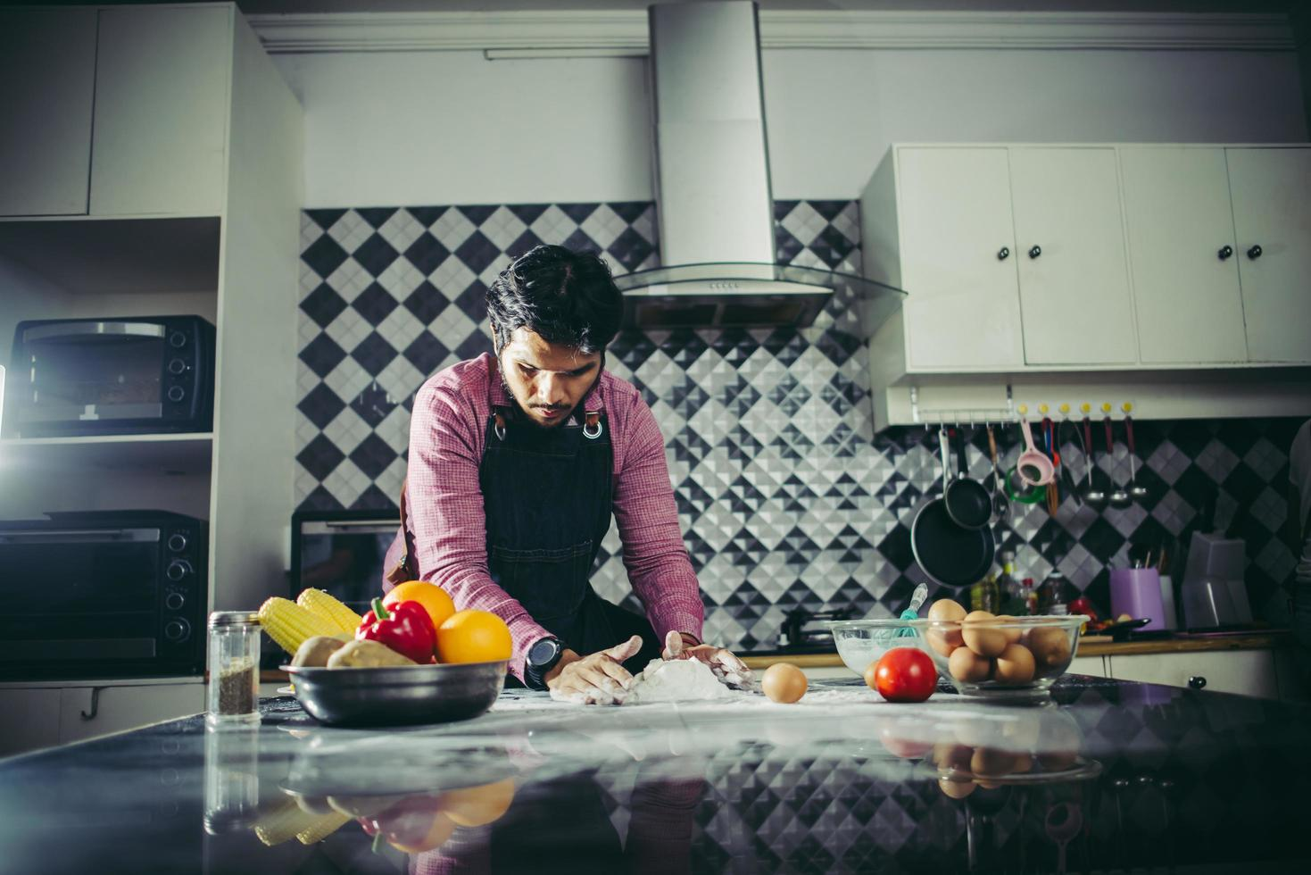 Hombre amasando masa de pizza casera en la cocina foto