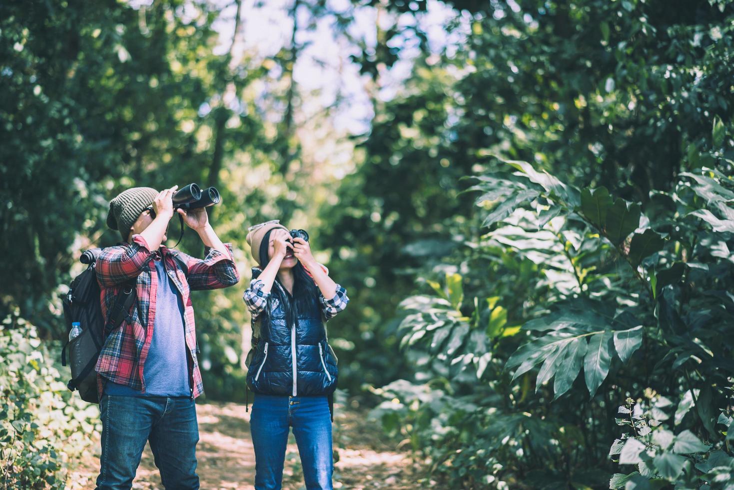 jóvenes excursionistas con binoculares en el bosque foto