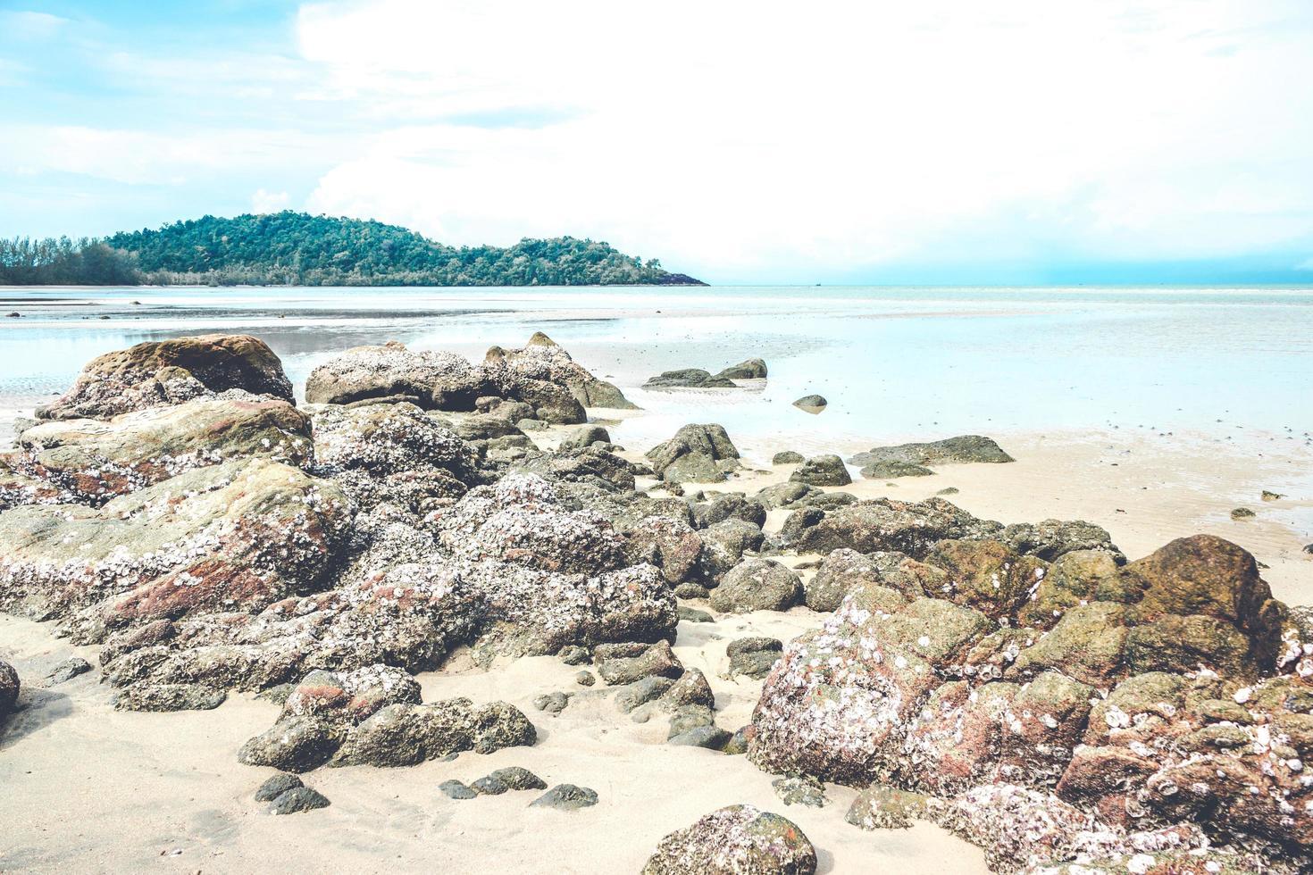 Rocks on beach with cloudy blue sky photo