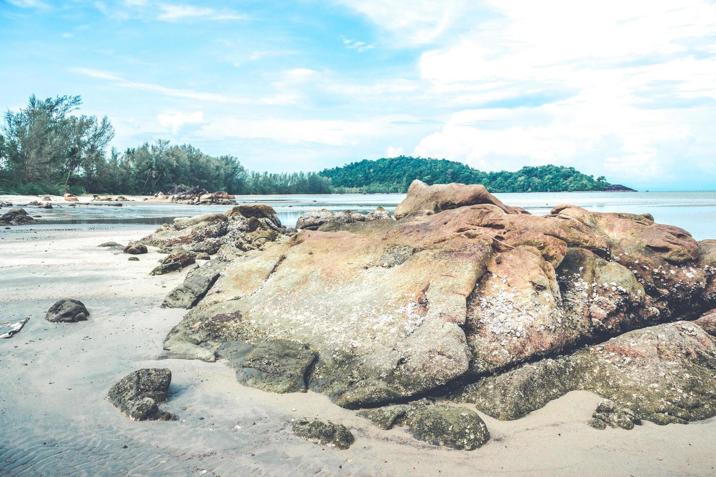 rocas en la playa con nublado cielo azul foto