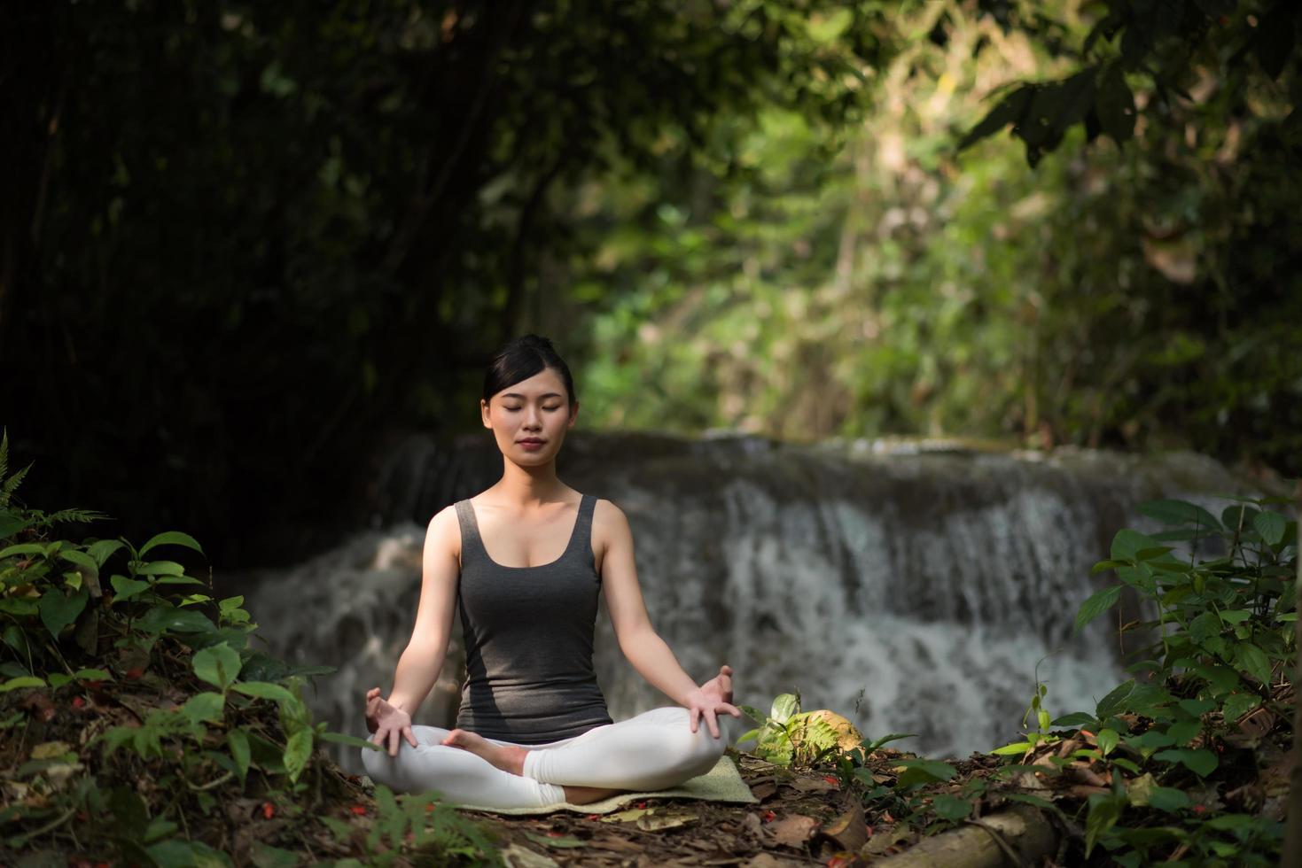 mujer joven en una pose de yoga sentado cerca de una cascada foto