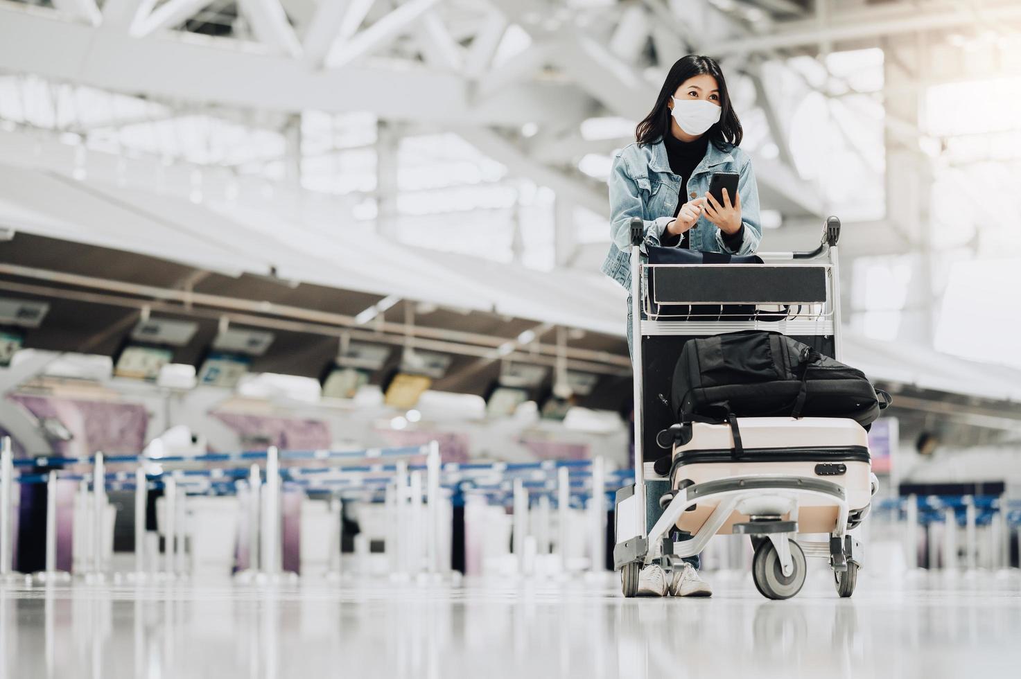 Mujer con máscara con carrito de equipaje foto