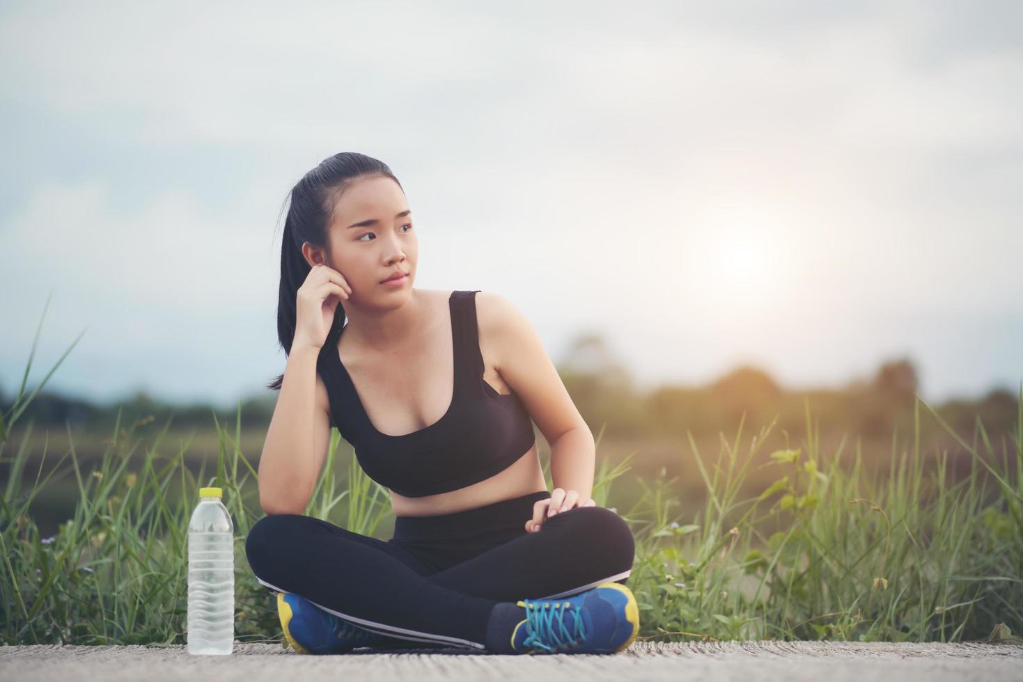 Corredor de fitness adolescente relajante con agua después del entrenamiento foto