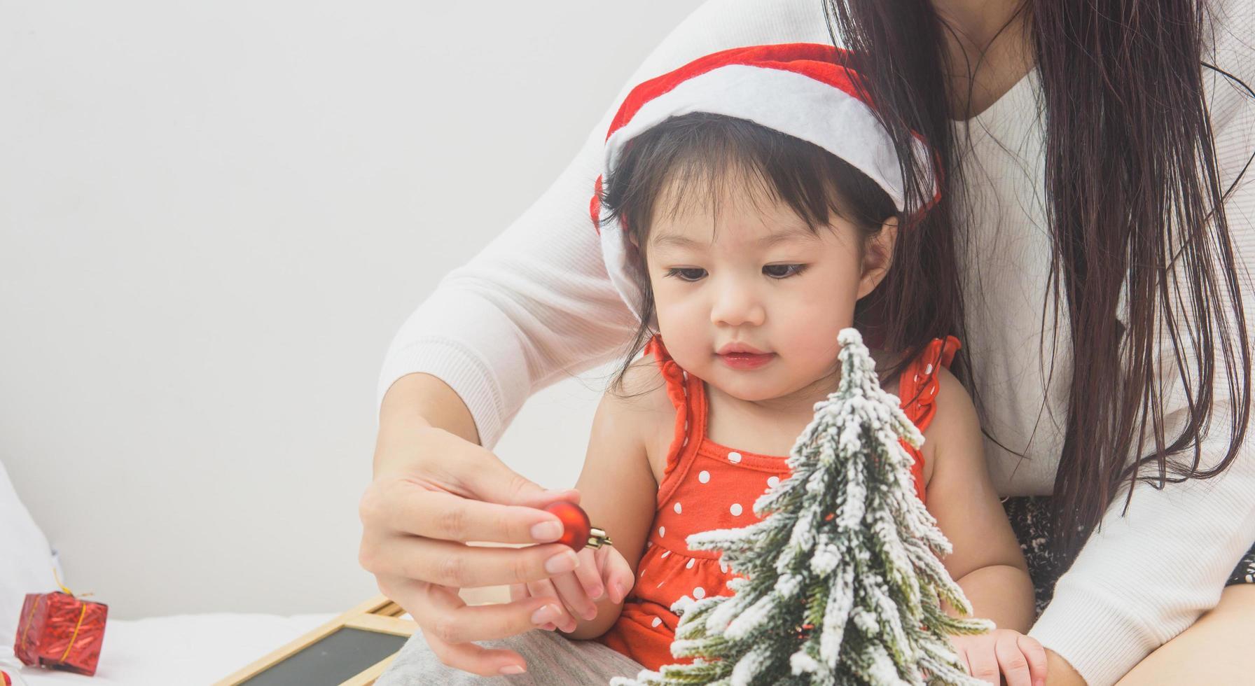 Madre de familia feliz y bebé jugando a casa en las vacaciones de Navidad foto