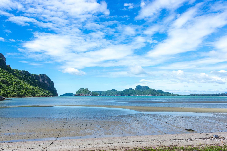 playa y montaña contra el cielo azul nublado foto