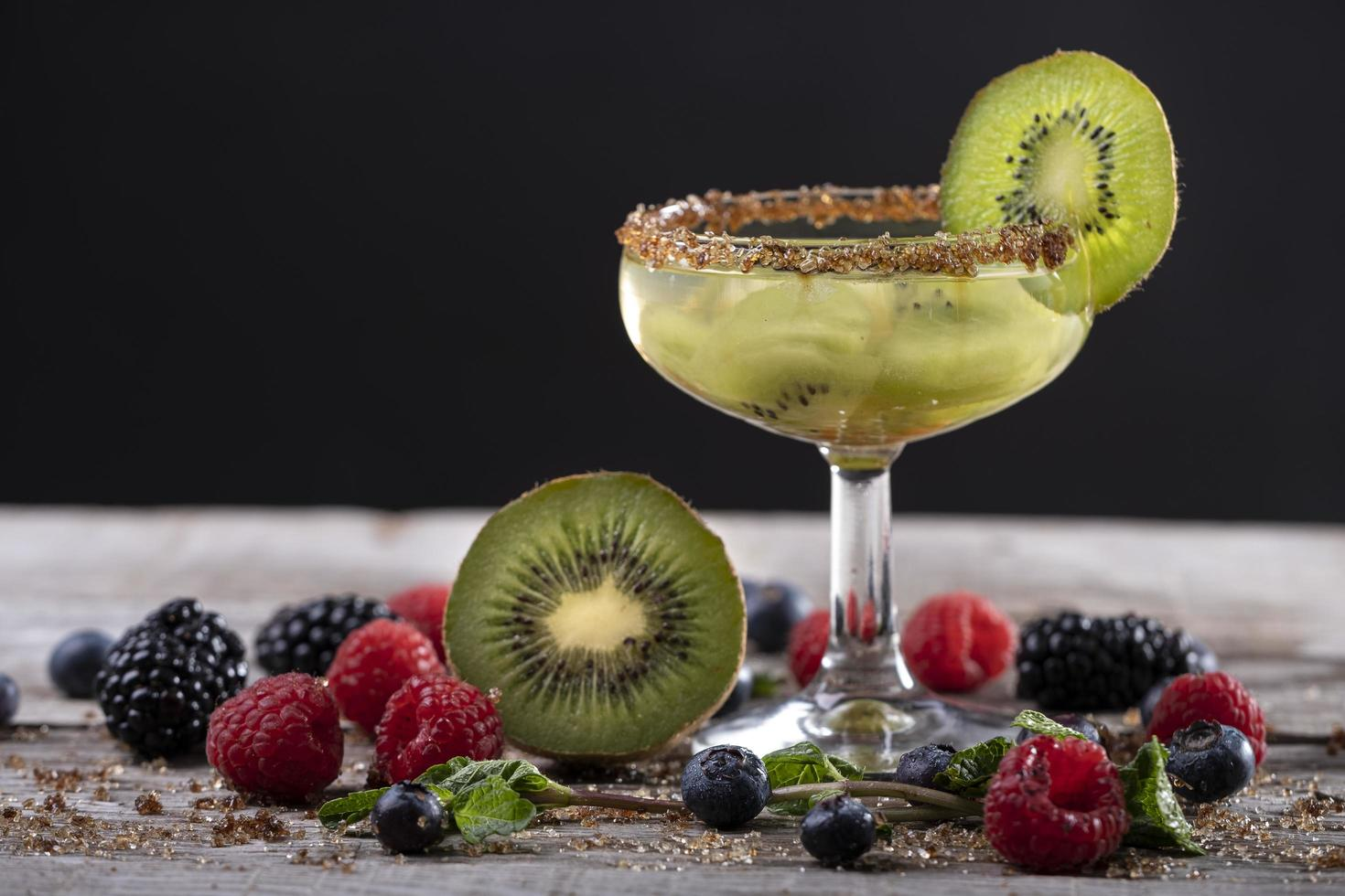 kiwi cocktail on a wooden base decorated with fruits of the forest photo