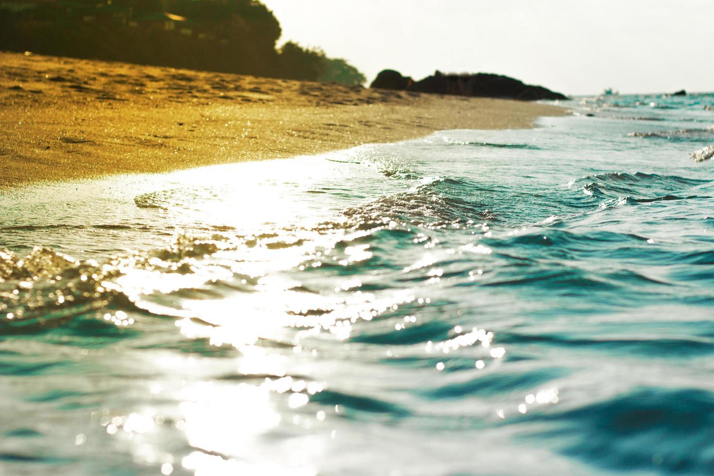 Arena y agua en la playa con cielo azul claro foto
